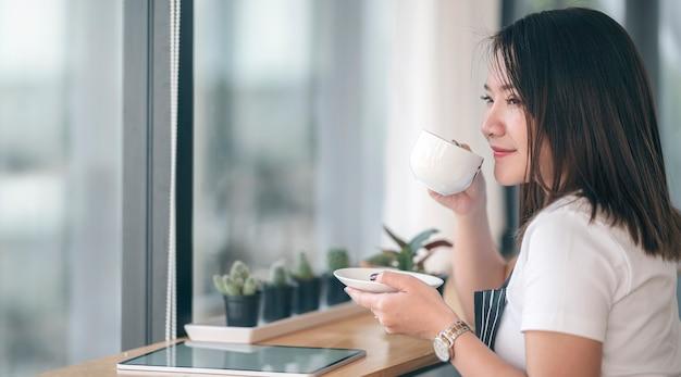 Portret van jonge mooie aziatische vrouw koffie drinken met geluk zittend in modern café.