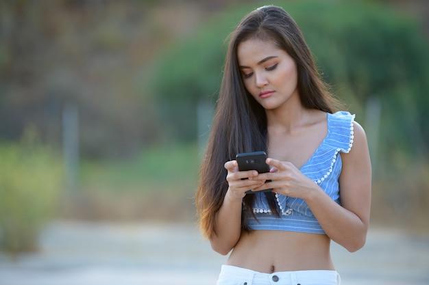 Portret van jonge mooie aziatische vrouw langs de kant van de weg