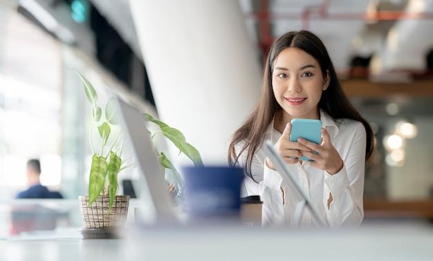 Portret van jonge mooie aziatische vrouw met behulp van smartphone op kantoor, glimlachend en camera kijken.