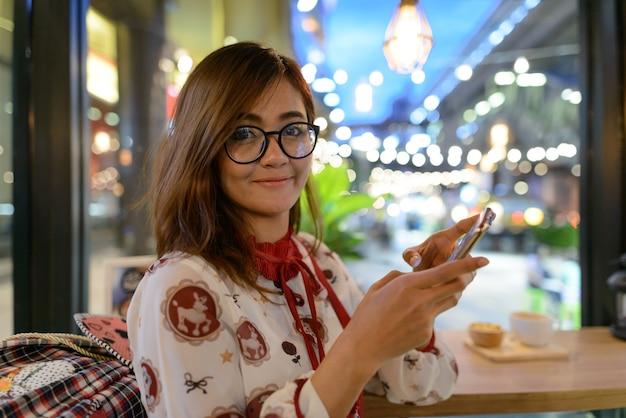 Portret van jonge mooie aziatische vrouw ontspannen in de koffieshop