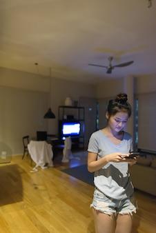 Portret van jonge mooie aziatische vrouw ontspannen in de woonkamer