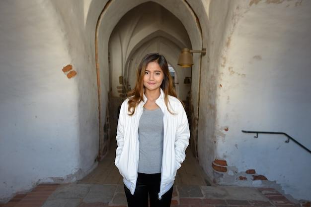 Portret van jonge mooie aziatische vrouw stond in de ingang binnenkant van historisch gebouw