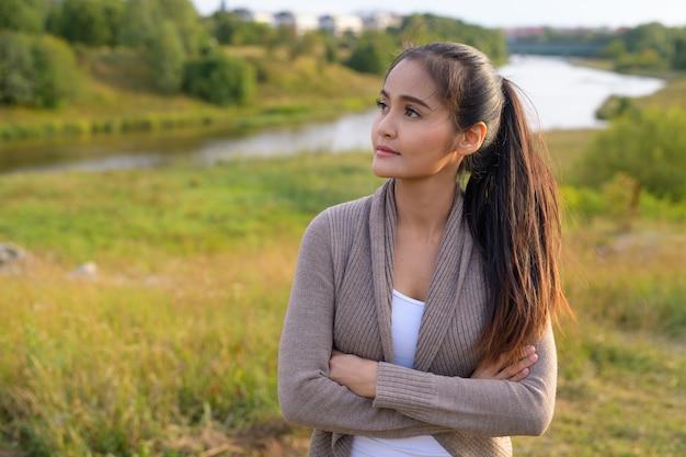 Portret van jonge mooie aziatische vrouw tegen ontspannen uitzicht op de rivier en het weelderige groene veld