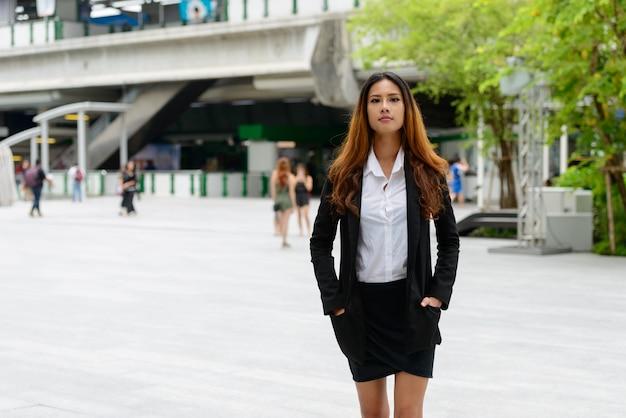 Portret van jonge mooie aziatische zakenvrouw in de straten van de stad buitenshuis