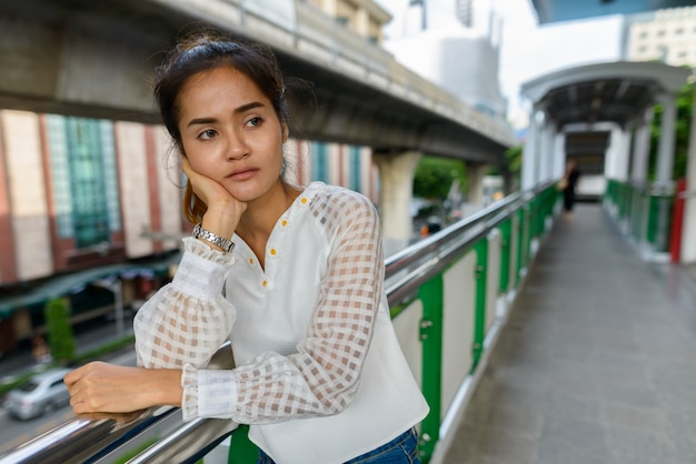 Portret van jonge mooie aziatische zakenvrouw op sky treinstation in de stad buitenshuis