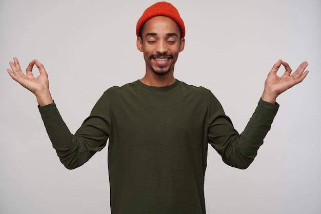 Portret van jonge mooie bebaarde donkerhuidige brunette man positief glimlachend en handen met mudra gebaar opheffen terwijl staande op wit, gekleed in vrijetijdskleding