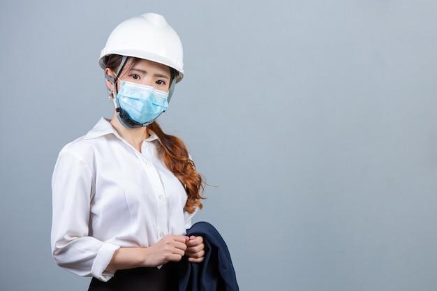 Portret van jonge mooie bedrijfsvrouw die gezichtsmasker op grijze oppervlakte dragen