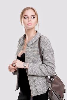 Portret van jonge mooie bedrijfsvrouwenblonde in zwarte kleding, jasje en met zak op grijze achtergrond