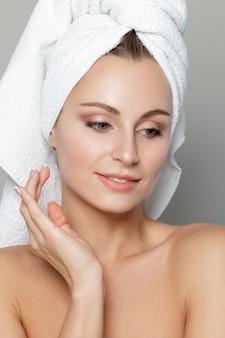 Portret van jonge mooie blanke vrouw wat betreft haar gezicht geïsoleerd op witte achtergrond.