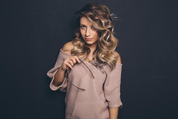 Portret van jonge mooie blond-haired trendy glazen en vrijetijdskleding dragen en het stellen over zwarte achtergrond