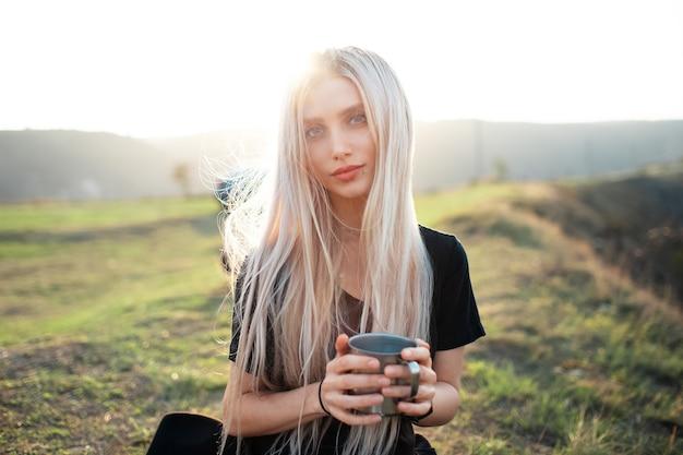 Portret van jonge mooie blonde meisje, met een warme stalen beker met thee op de achtergrond van de zonsondergang.