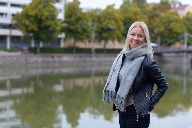 Portret van jonge mooie blonde scandinavische vrouw ontspannen bij de rivier