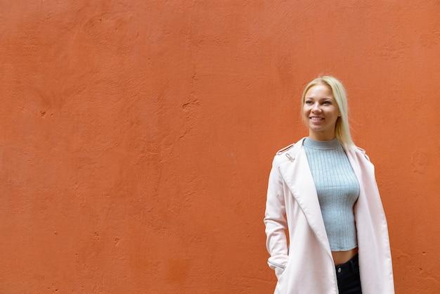 Portret van jonge mooie blonde scandinavische vrouw tegen oranje betonnen muur buitenshuis