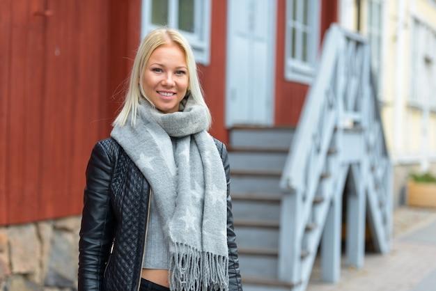 Portret van jonge mooie blonde scandinavische vrouw tegen rode houten gebouw buitenshuis