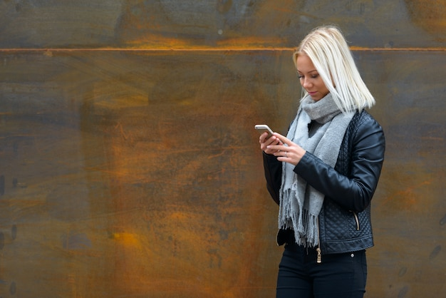 Portret van jonge mooie blonde scandinavische vrouw tegen roestige oude metalen wand buitenshuis
