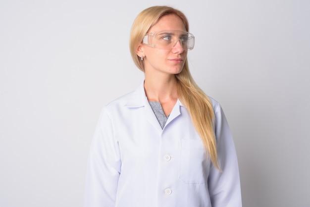 Portret van jonge mooie blonde vrouw arts als wetenschapper beschermende bril op wit