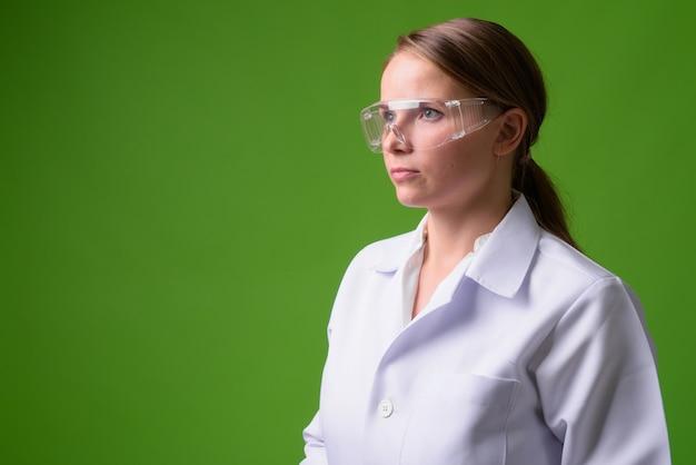 Portret van jonge mooie blonde vrouw arts beschermende bril op groen