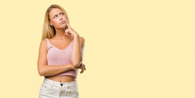 Portret van jonge mooie blonde vrouw denken en opzoeken, verward over een idee, zou proberen een oplossing te vinden