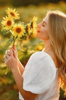 Portret van jonge mooie blonde vrouw in zonnebloemen veld in tegenlicht. zomer platteland concept. vrouw en zonnebloemen. zomer licht. buiten schoonheid.