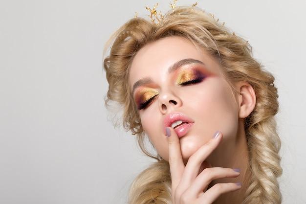 Portret van jonge mooie blonde vrouw met creatieve make-up en twee franse vlechten die gouden kroon dragen. veelkleurige smokey eyes
