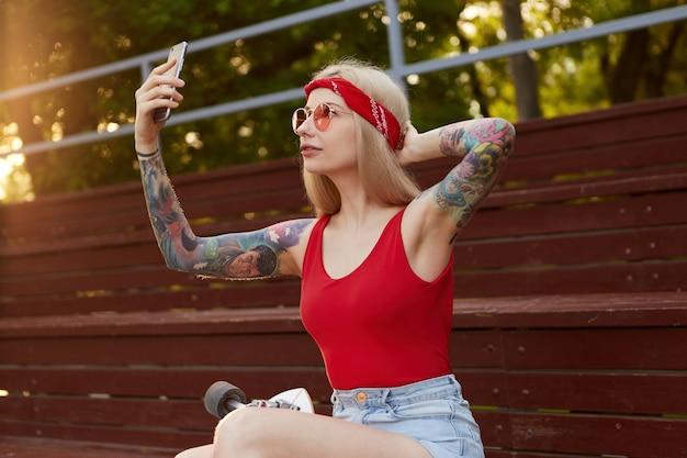 Portret van jonge mooie blonde vrouw met getatoeëerde armen in een rood t-shirt en denim shorts, met een gebreide bandana op het hoofd, in rode glazen, smartphone houden en maakt selfie