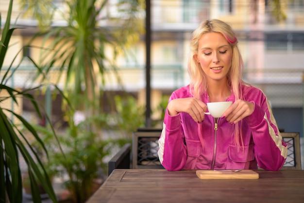 Portret van jonge mooie blonde vrouw ontspannen in de koffieshop