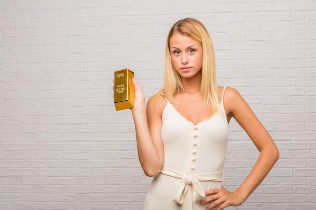 Portret van jonge mooie blonde vrouw tegen een bakstenen muur die iets met handen houdt