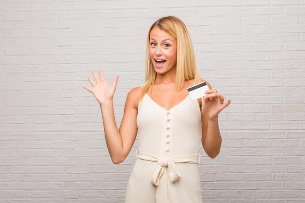 Portret van jonge mooie blonde vrouw tegen een bakstenen muur gelukkig gillen