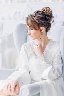 Portret van jonge mooie bruid in elegante witte robezitting op een stoel in een helder binnenland