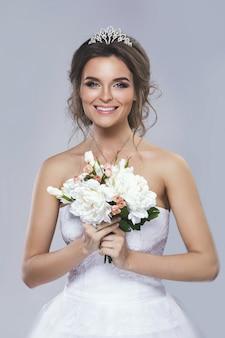 Portret van jonge mooie bruid met boeket bloemen