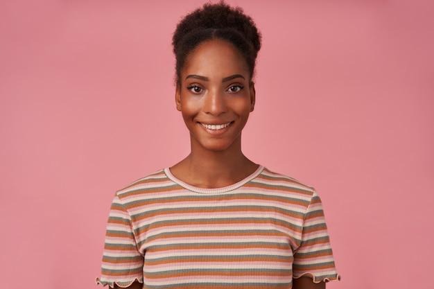 Portret van jonge mooie bruinharige krullende dame met het tonen van haar witte perfecte tanden terwijl ze gelukkig naar voren kijkt, geïsoleerd over roze muur