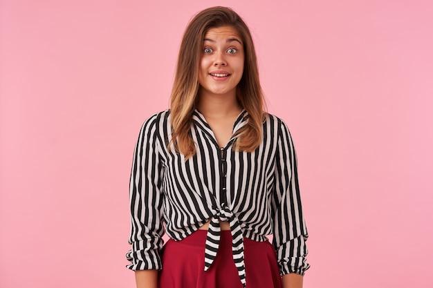 Portret van jonge mooie bruinharige vrouw met open ogen die verrast wenkbrauwen optrekt terwijl ze positief kijkt, gekleed in feestelijke kleding terwijl ze poseren op roze