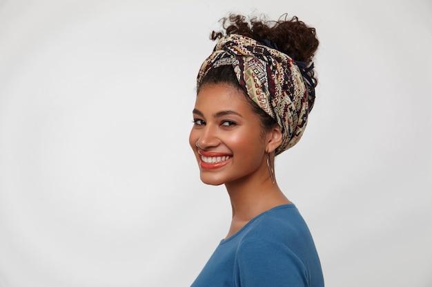 Portret van jonge mooie bruinogige krullende donkere huid dame die haar witte perfecte tanden toont terwijl ze gelukkig naar de camera lacht, geïsoleerd op witte achtergrond