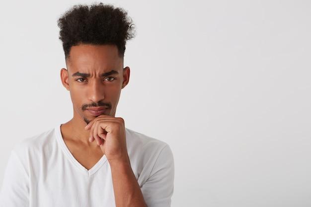 Portret van jonge mooie brunette bebaarde man met donkere huid met zijn kin