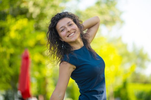 Portret van jonge mooie brunette geniet van een heldere zomerdag in het groene park