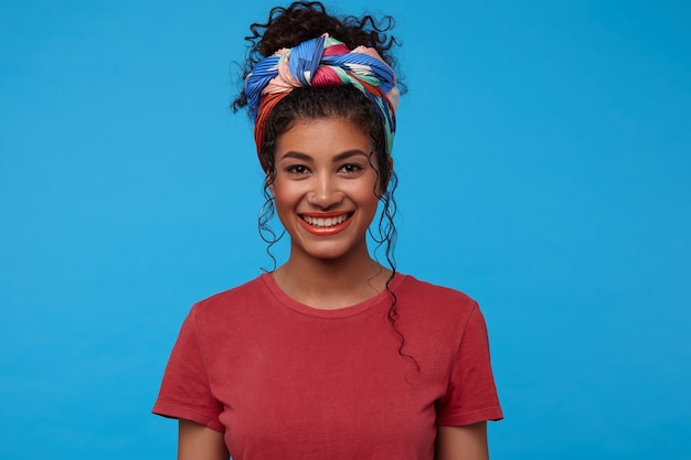 Portret van jonge mooie brunette krullende vrouw met feestelijke make-up vrolijk op zoek naar voorzijde met charmante glimlach, staande tegen blauwe muur