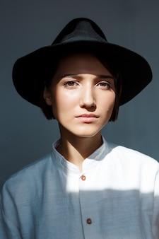 Portret van jonge mooie brunette meisje in zwarte hoed.