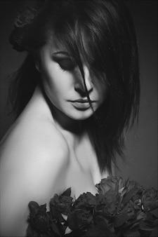 Portret van jonge mooie brunette met kleine rode rozen