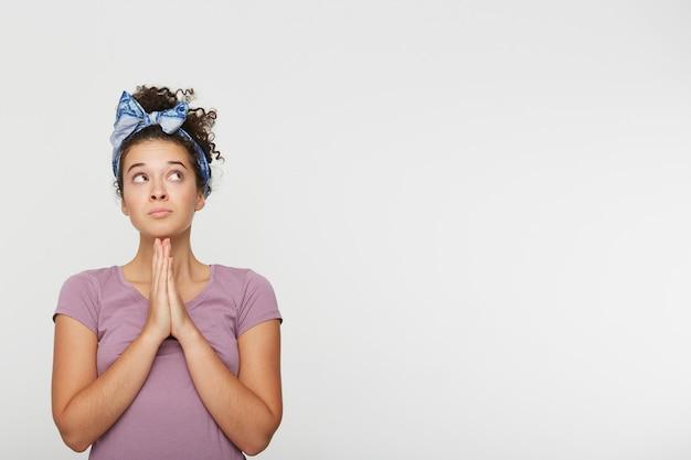 Portret van jonge mooie brunette vrouw bidden, handen gevouwen in gebed concept