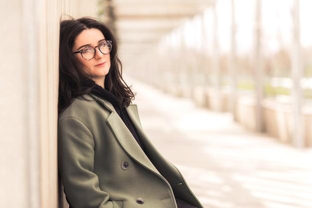 Portret van jonge mooie brunette vrouw in glazen, zwarte hoodie en groene jas poseren op straat.