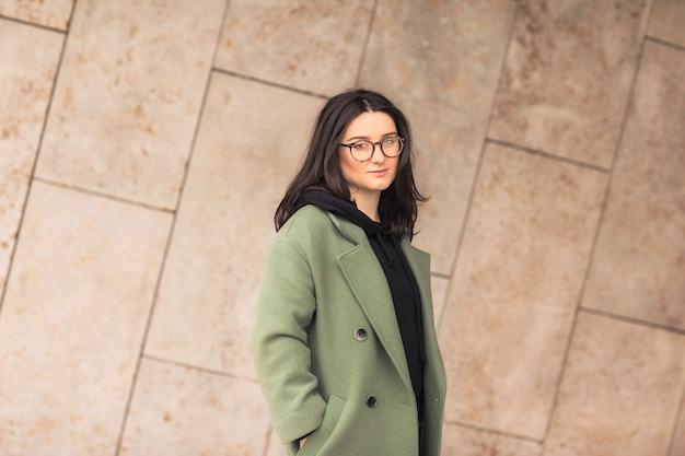 Portret van jonge mooie brunette vrouw in glazen, zwarte hoodie en groene jas poseren tegen straatmuur.