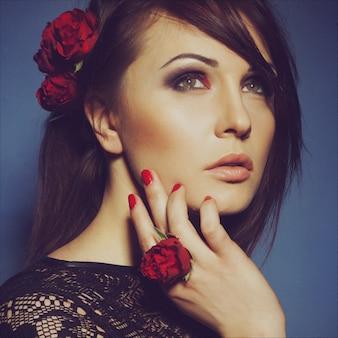Portret van jonge mooie brunette vrouw met kleine rode rozen in zwarte jurk