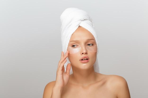 Portret van jonge mooie dame met witte handdoek op hoofd met flarden onder ogen