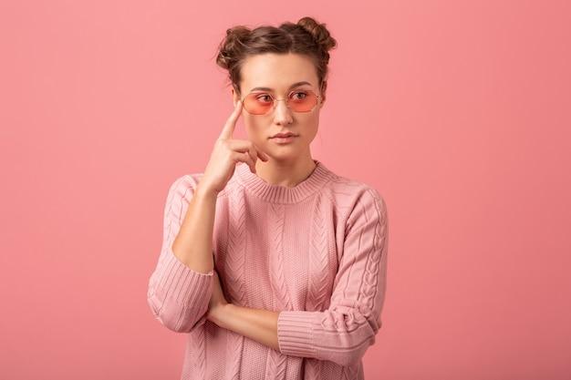 Portret van jonge mooie denkende vrouw in roze trui en zonnebril geïsoleerd op roze studio achtergrond close-up