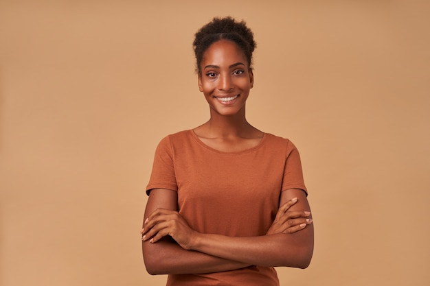 Portret van jonge mooie donkere gekrulde dame houdt haar handen gekruist met charmante glimlach, staande op beige
