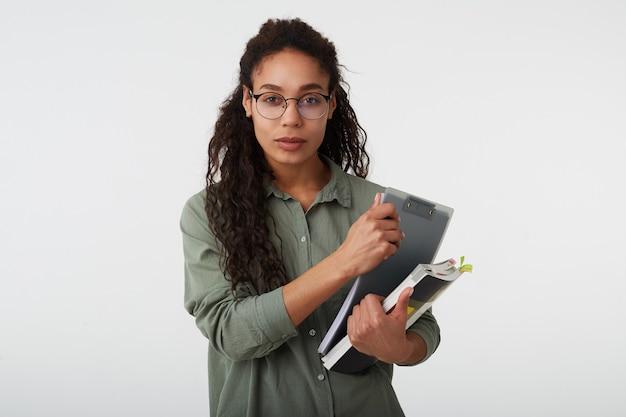 Portret van jonge mooie donkerharige gekrulde vrouw met donkere huid die boeken houdt en rustig kijkt met gevouwen lippen, geïsoleerd op wit