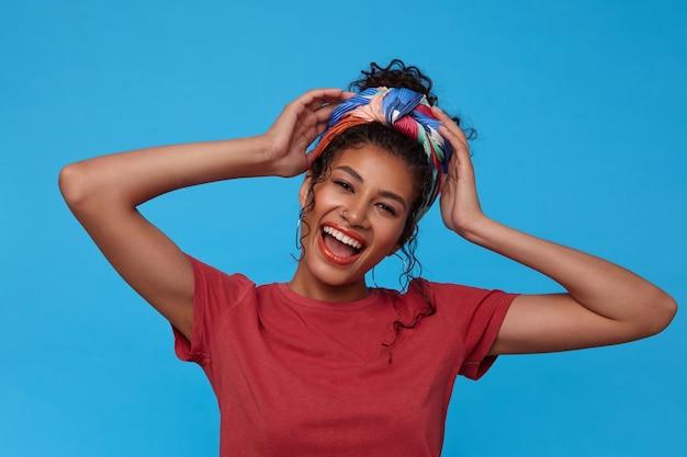 Portret van jonge mooie donkerharige krullende vrouw met feestelijke make-up die gelukkig lacht en emotioneel handen opheft naar haar hoofd, geïsoleerd over blauwe muur