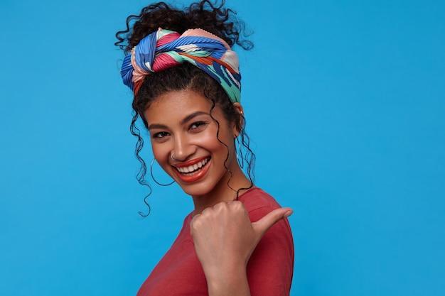 Portret van jonge mooie donkerharige krullende vrouw met feestelijke make-up die met opgeheven hand naar achteren duimen en gelukkig aan de voorkant glimlacht, staande over blauwe muur