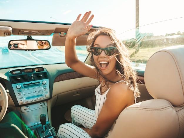 Portret van jonge, mooie en lachende hipster-vrouw en haar vriendje in cabriolet