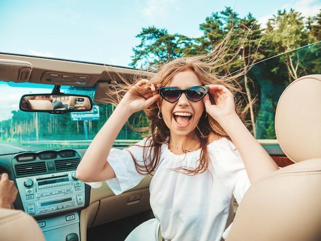 Portret van jonge mooie en lachende hipster vrouw in converteerbare auto